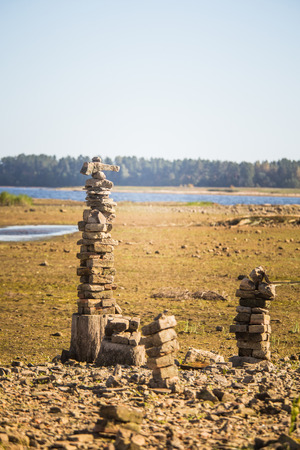 Sunny riverside landscape of a dried river bed and rocks. Stone balancing constructions near the river.  Rocky river landscape. Stock Photo