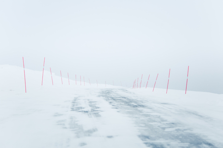 A beautiful white snowy road in central Norway with a red safety poles. Minimalist winter scenery un northern Europe. Stock Photo