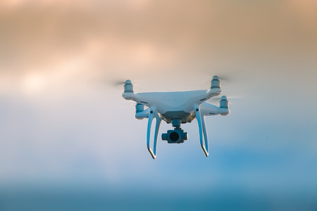 A beautiful flying drone in the evening skies. Aero photography in action. White drone flying.