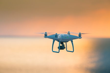 A beautiful flying drone in the evening skies. Aero photography in action. White drone flying. Banco de Imagens - 97930257