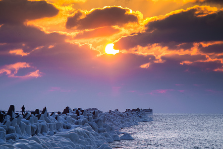 A beautiful evening landscape of a frozen breakwater in the Baltic sea. Winter landscape at the beach. Vivid colors. Stock Photo