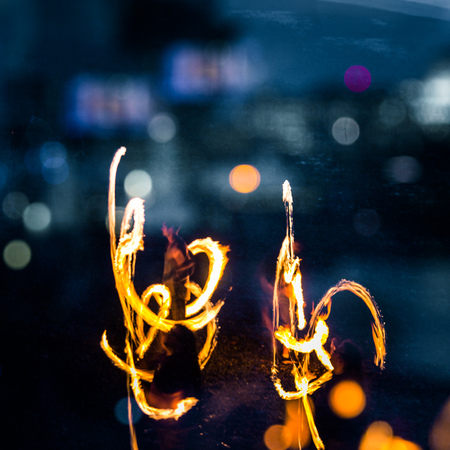 A beautiful, abstract scene of fire spinners in London at the bank of Thames. Nighttime performance. Light painting.