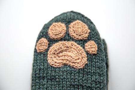 A beautiful closeup od a knitted wool socks with a crocheted animal paw pattern.