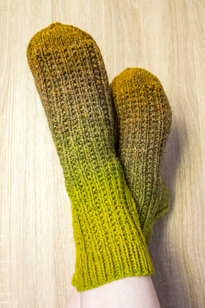 A woman wearing warm hand craft socks. Knitted form a natural sheep wool yarn. Winter clothing. On a wooden background.