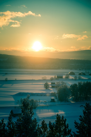 A beatiful sunset landscape of a small Norwegian ton Roros. WInter scenery with an evening sun. Warm, relaxing atmosphere.