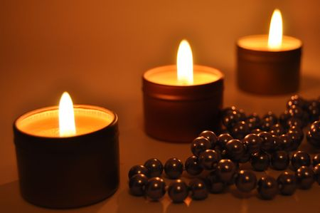 gladden: Close up of a burning candles with pearls Stock Photo