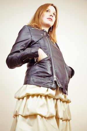 portrait of an attractive beautiful blond woman in a dress and black leather jacket photo