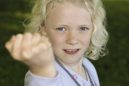 annoyance: Young blond girl showing her fist