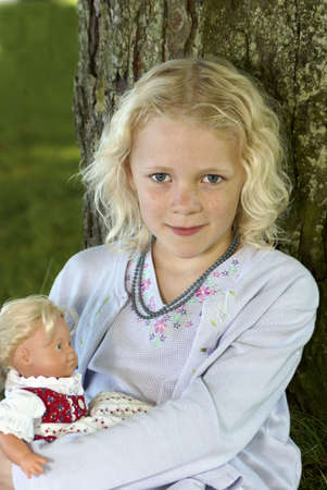 cary: Young beautiful kid holding doll and smiling Stock Photo