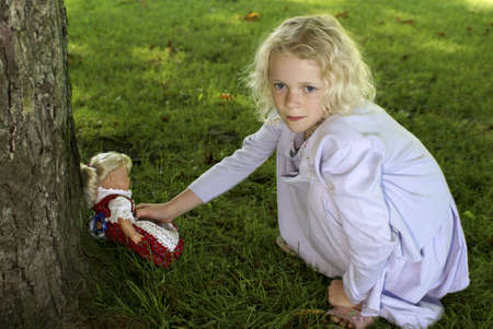 cary: Young beautiful kid reaching for a lost doll Stock Photo