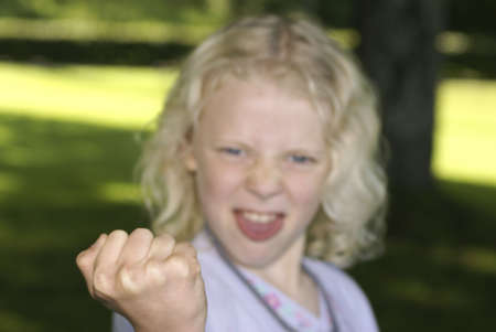 Young blond girl showing her fist and making faces Stock Photo - 3486059