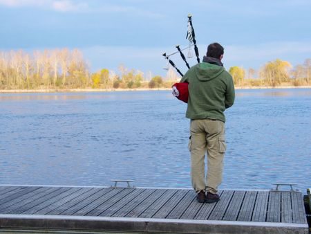 Bagpiper playing alone on the bank of the French river Loire