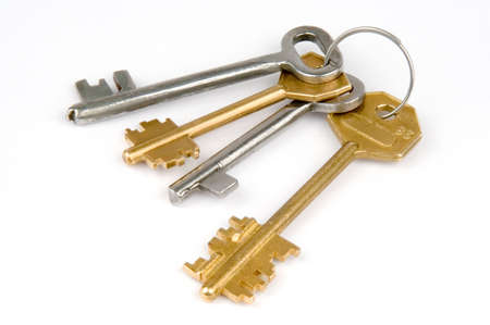 bunch of four yellow and silver metallic keys over white background