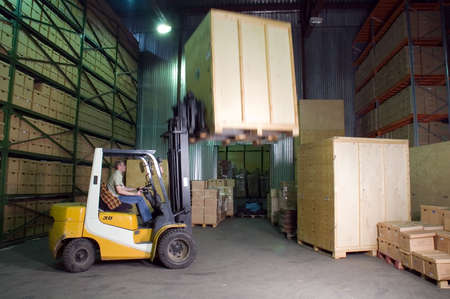 forklifts: Man working on the truck in the warehouse