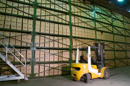 stow: Truck in the warehouse. Boxes on the shelves in the background. Stock Photo