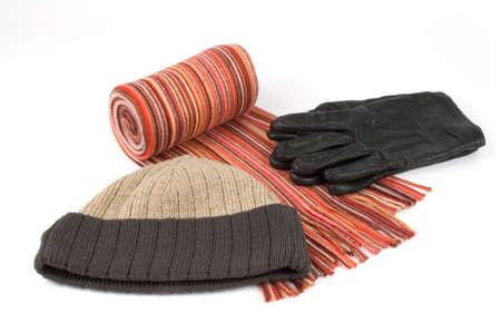 shawl: Gedraaid meerkleuren wollen sjaal, pet ang zwarte handschoenen over witte achtergrond