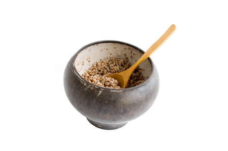 corrode: The cast-iron pot with spoon and boiled buckwheat isolated over white