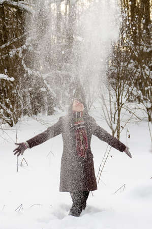 Young woman is playing with falling snow in the winter forest photo