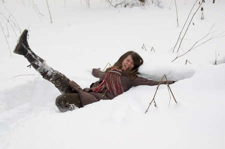 Young woman is lie in the snow in the winter forest photo