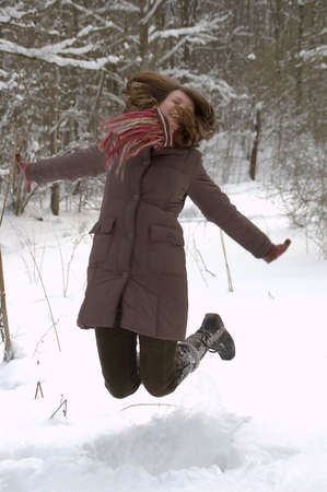 Young woman is jumping over snow in the winter forest photo