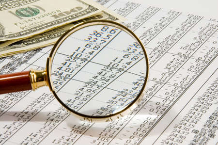 Looking through magnifying glass to the dollars banknotes and financial report Stock Photo