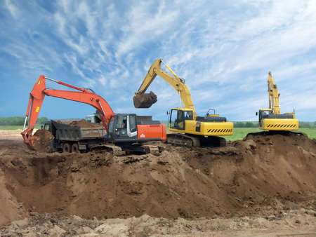 loads: Three excavators working in the field, one of them loads the ground in the truck. Above them the beautiful sky. Stock Photo