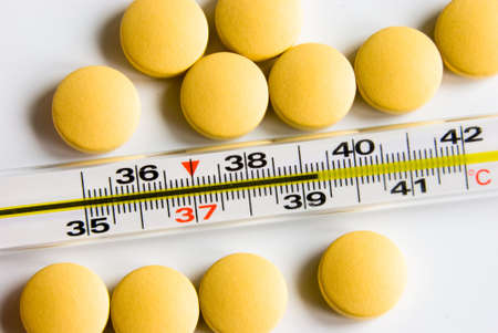 Medical thermometer indicated high temperature and yellow pills over white background photo
