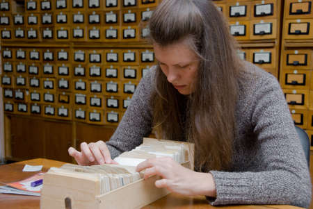 card index: Young woman searching file in the library card index. Stock Photo