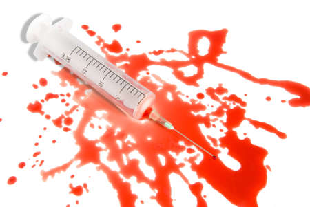 Medical syringe in the spatter blood puddle over white background. Small blood drop on the needle end.