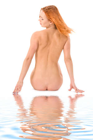 aqua naked: Lovely redhead lady sitting on white sand near the blue water