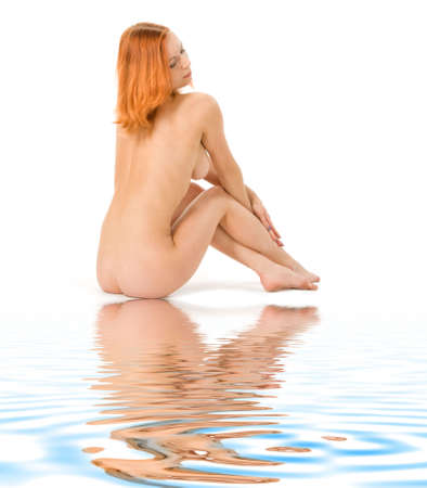aqua naked: Pretty redhead lady sitting on white sand near the water Stock Photo