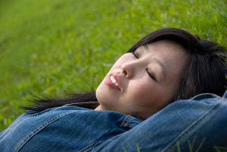 Dreams in the grass - young attractive woman  relaxes in the park photo