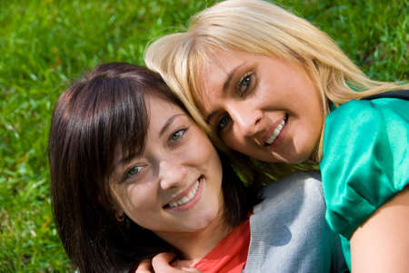 Happy blonde and brunette embrace on the grass Stock Photo