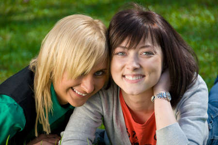 lesbian love: Happy blonde and brunette  portrait on the nature background