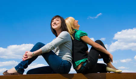 Blonde and brunette sit back to back on the sky background and dream of something beautiful