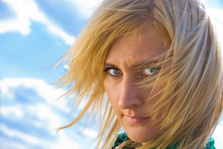 flyaway: Stylish cute blonde with fly-away hair. Portrait on sky background. Stock Photo