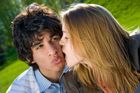 Happy pair of lovers play and kiss in the park photo