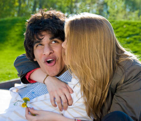 Happy pair of lovers embrace and kiss in the park photo