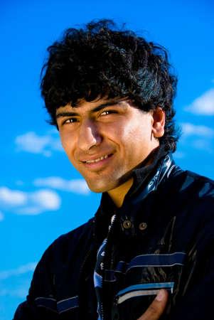 Arabian guy portrait over blue sky background