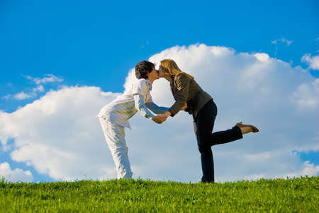 Young couple kissing on the lawn over sky background photo