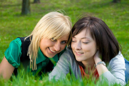lesbian relationship: Happy blonde and brunette rest on the nature  Stock Photo