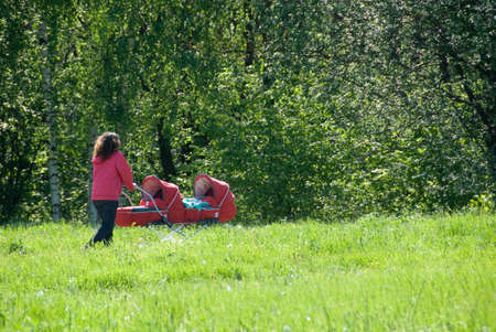 Young mother walking in a nature with twin carriage photo