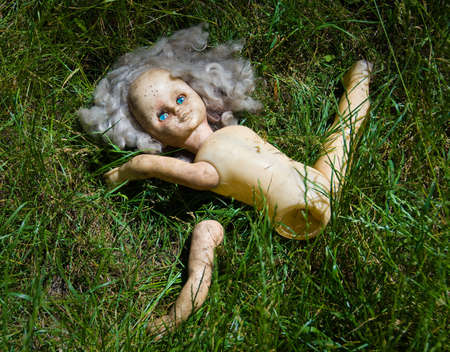 odd: Partitioned blonde doll with blue eyes lie in the grass