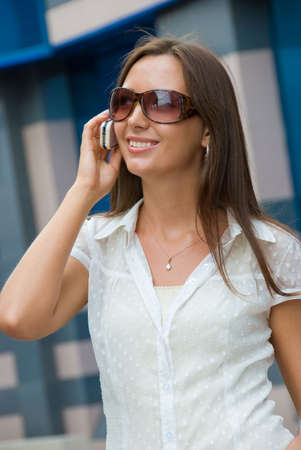 Cute smiling girl speaks on  a mobile phone photo