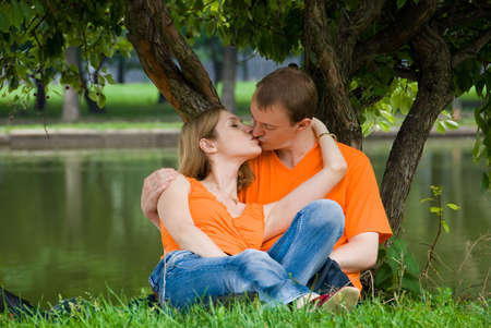 sexual woman: Loving couple kisses under a tree on a river bank