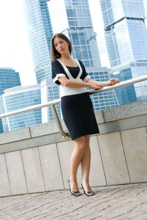 Young business woman poses outdoors. Modern buildings on the background. photo