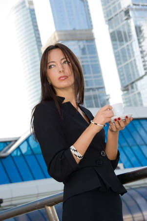 Business woman drinks a coffee outdoors in modern downtown photo