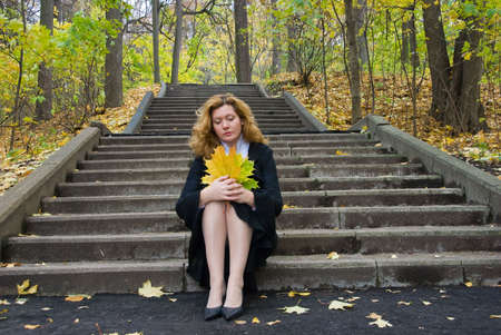 Middle age woman in depression on an autumn nature photo