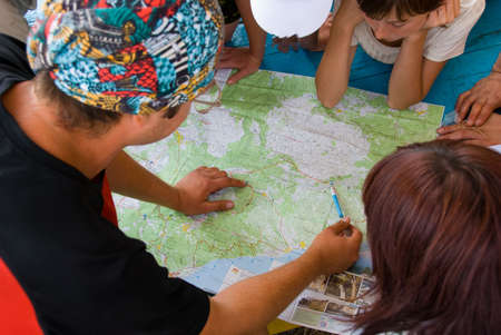 group direction: Hikers group planning path on the map