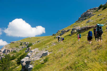 Group of hikers clamber in mountains photo